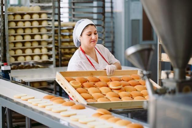 Förderband in einer bäckerei mit frisch gebackenen brötchen