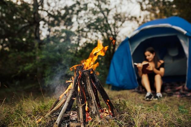 Fokus auf bonfire. junge frau, die im zelt sitzt und buch im lager nahe einem lagerfeuer liest.