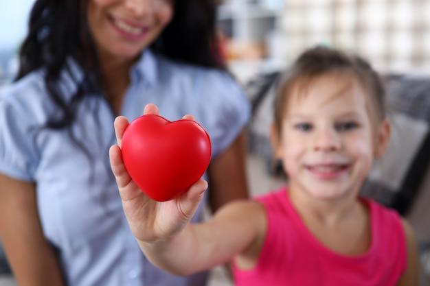 Fokus auf kinderhand, die spielzeug rotes herz hält. liebevolle beziehung zwischen mutter und tochter. glückliches mädchen mit glück. familien- und mutterschaftskonzept