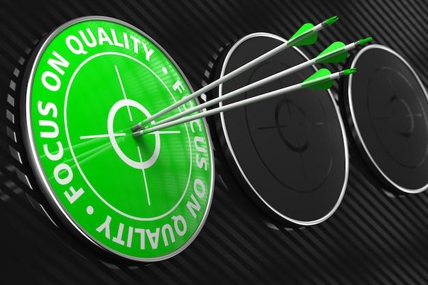 Fokus auf qualitätsslogan. drei pfeile, die das zentrum des grünen ziels auf schwarzem hintergrund treffen.