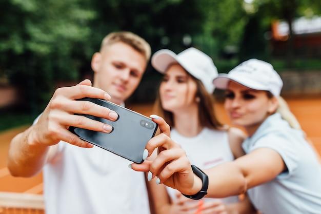 Fokus auf tennisspieler machen selfie am telefon.