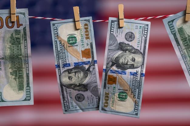 Fokus der dollarbanknoten, die am seil auf amerikanischem flaggenhintergrund hängen. finanzkrise