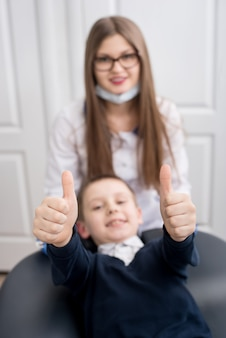 Fokus der hände des jungen zeigt daumen hoch gesten der guten klasse. arzt und kind schauen in die kamera