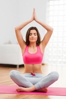 Fokus frau, die yoga zu hause macht