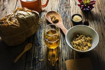 Fokus-Stellen-Chrysanthemen-Tee und getrocknete Chrysantheme auf einem alten Holztisch.