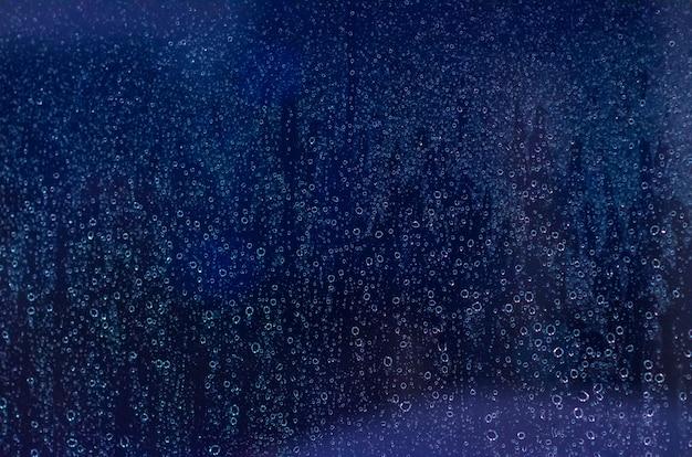 Fokus und unscharfes foto des regens fallen auf glasfenster mit dunkelblauem