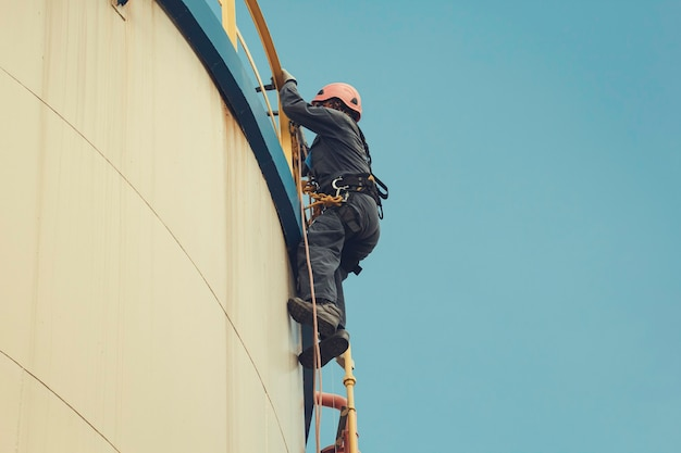 Fokusansicht männlicher arbeiter in der höhe des tankseilzugangs sicherheitsinspektion der dickenlageröl- und gastankindustrie