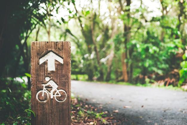 Fokussieren sie fahrrad- oder fahrradwegzeichenpfosten im grünen baum mit bokeh sonnenlichthintergrund.