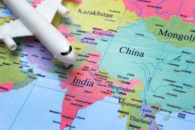 Fokussieren sie flugzeugspielzeug auf indien-land auf der karte im reisekonzept