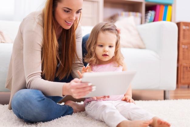 Fokussieren sie frau mit kleinem mädchen unter verwendung der digitalen tablette