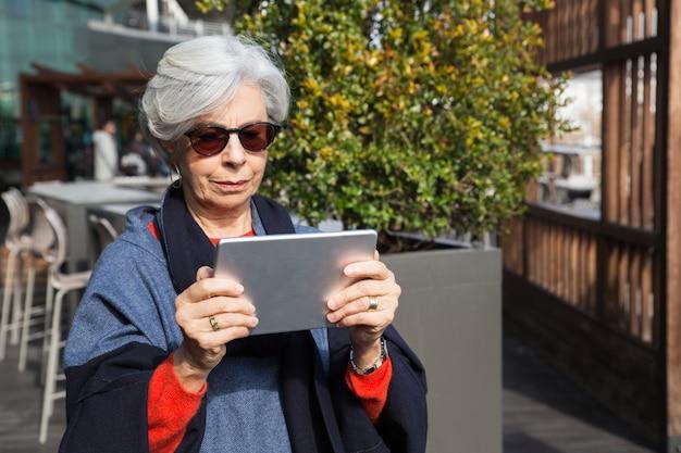 Fokussierte ältere dame, die elektronische karte konsultiert