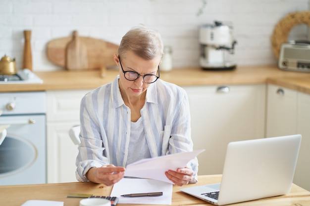 Fokussierte ältere frau mit brille, die mit dokumenten arbeitet, während sie in der modernen küche sitzt