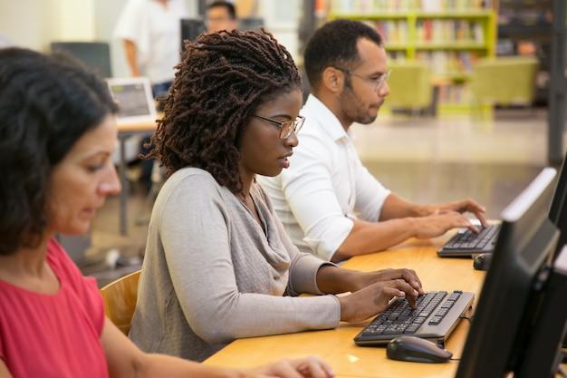 Fokussierte afroamerikanerfrau, die auf computertastatur schreibt