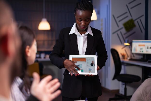 Fokussierte afroamerikanische geschäftsfrau, die firmendiagramme auf tablet zeigt