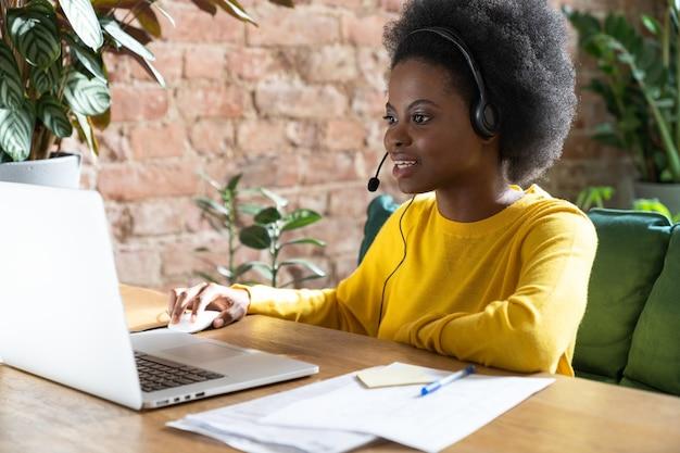 Fokussierte afroamerikanische mitarbeiterin, die ein headset trägt, im büro am laptop arbeitet und ein webinar sieht