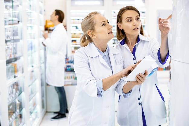 Fokussierte apothekerinnen, die vor einer glasvitrine in einer apotheke stehen und eine tablette halten, überprüfen