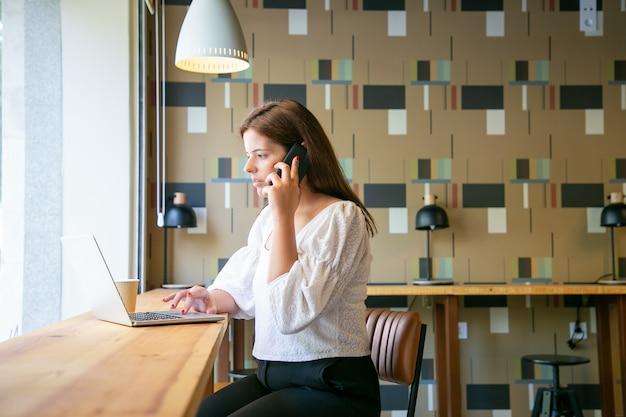 Fokussierte brünette frau, die laptop verwendet und auf smartphone spricht