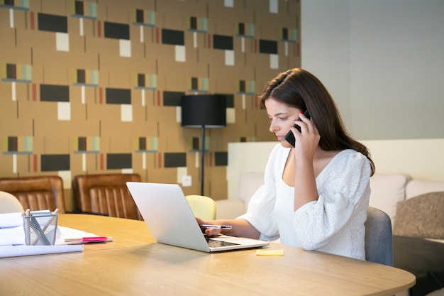 Fokussierte designerin, die das projekt mit dem kunden am telefon bespricht, mit laptop und blaupausen am tisch sitzt und tippt