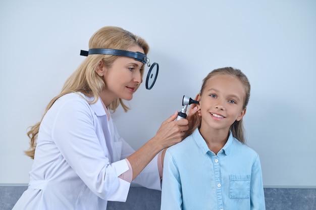 Fokussierte, erfahrene blonde hno-arztin mittleren alters, die mit einem kopfspiegel und einem otoskop in den gehörgang der jungen mädchen schaut