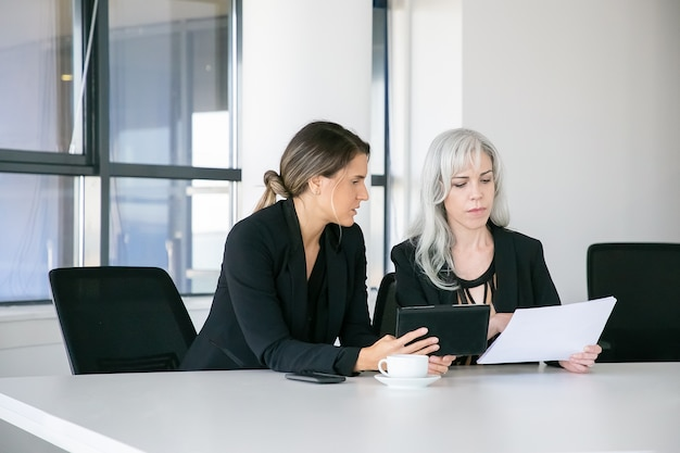Fokussierte fachleute, die gemeinsam berichte analysieren. zwei geschäftsfrauen sitzen zusammen, lesen dokumente, benutzen tablette und sprechen. teamwork-konzept