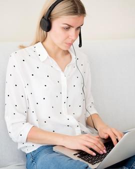 Fokussierte frau, die auf laptop-e-learning-konzept schreibt