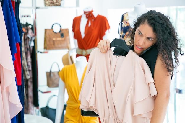 Fokussierte frau, die auf zelle spricht, während sie im modegeschäft einkauft, kleid auf sich selbst anwendet und im spiegel schaut. mittlerer schuss. boutique-kunden- oder einzelhandelskonzept