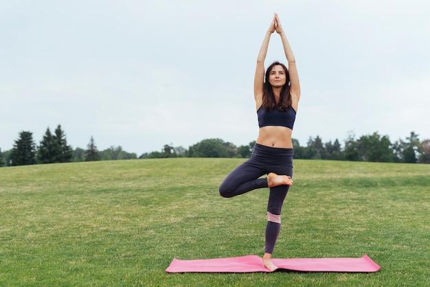 Fokussierte frau, die draußen yoga tut