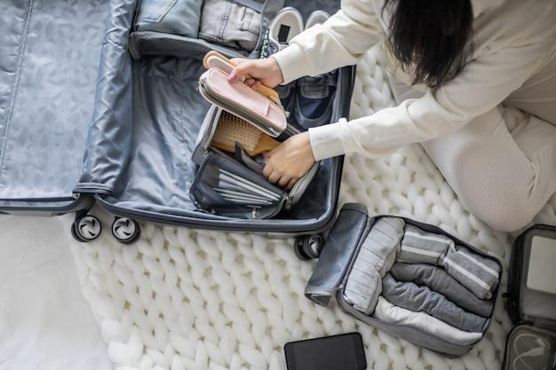 Fokussierte frau, die liste packt kofferorganisation kleidung kosmetiktasche für ausrüstung