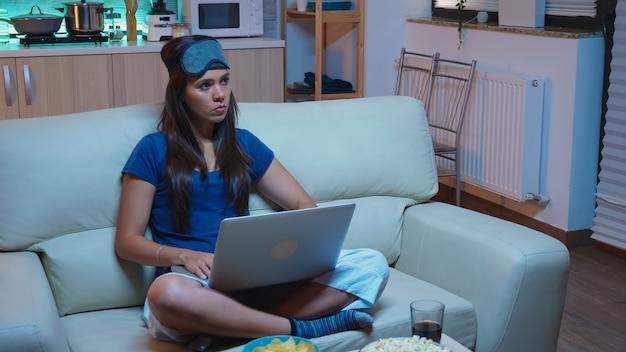 Fokussierte frau in pyjamas und maske zum schlafen auf der stirn, die spät in der nacht eine e-mail mit laptop schreibt. freiberufler, der von zu hause aus arbeitet, während er fernsieht und mit internet-technologie sucht
