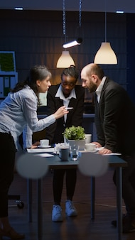 Fokussierte führungsfrau betritt den besprechungsraum im büro, lehnt sich am konferenztisch an und führt spät in der nacht eine brainstorming-unternehmenspräsentation durch. vielfältige multiethnische teamarbeit zur lösung von managementstrategien
