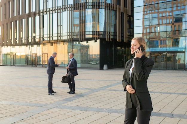 Fokussierte geschäftsfrau, die büroanzug trägt und im freien auf handy spricht. geschäftsleute und stadtbauglasfassade im hintergrund. speicherplatz kopieren. geschäftskommunikationskonzept