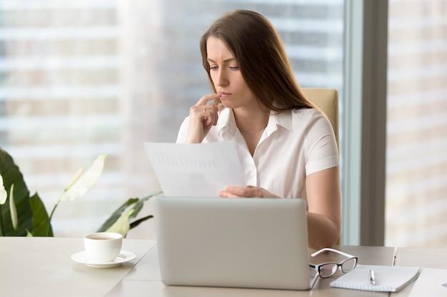 Fokussierte geschäftsfrau, die dokument analysiert und finanzbericht am arbeitsplatz hält