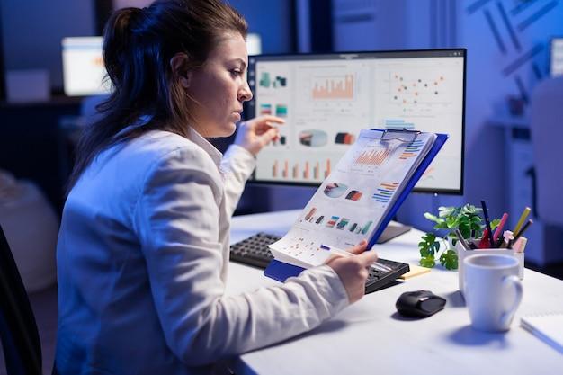 Fokussierte geschäftsfrau, die grafiken aus dem nootebook überprüft und an der finanzstrategie von büroangestellten arbeitet. vielbeschäftigter manager, der eine moderne technologienetzwerk-wireless-suche-geschäftslösung verwendet