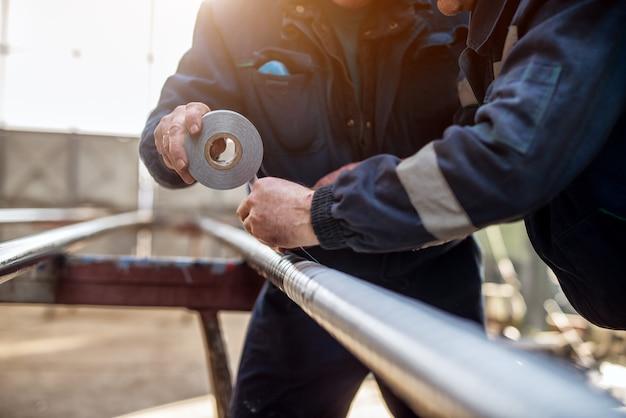 Fokussierte handansicht von professionellen industriearbeitern im gleichmäßigen verbinden von metallrohr mit klebeband.