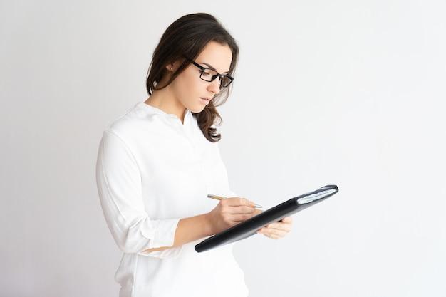 Fokussierte hübsche frau, die datei und schreiben hält. business lady arbeiten.