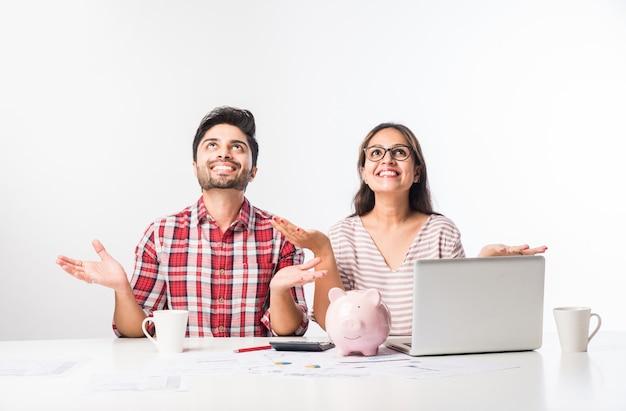 Fokussierte indische junge paarbuchhaltung, rechnungen berechnen, budgetplanung gemeinsam mit online-banking-diensten und rechner besprechen, finanzen prüfen