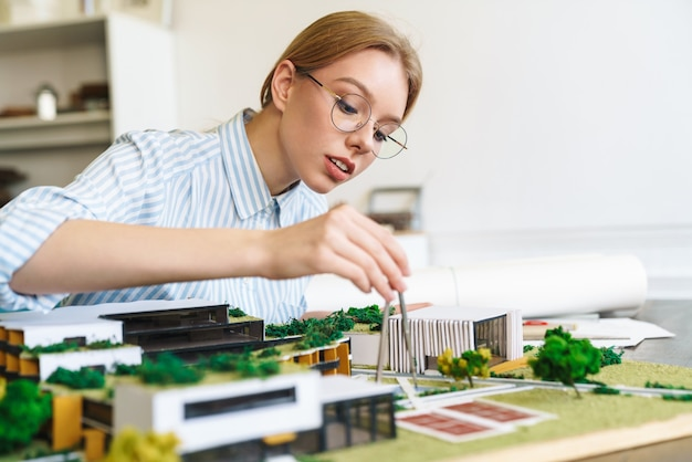 Fokussierte junge architektin in brillen, die entwurf mit hausmodell entwirft und am arbeitsplatz sitzt