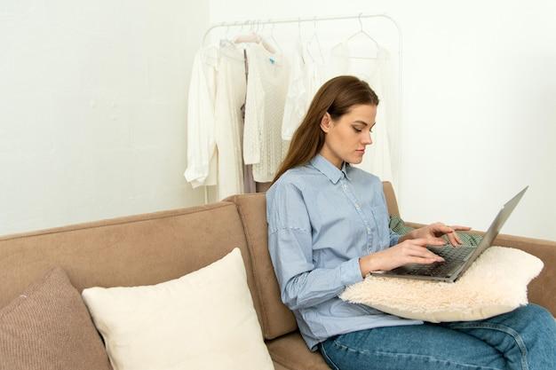 Fokussierte junge frau, die von zu hause aus bei der fernarbeit arbeitet. schöne junge frau, die unter verwendung des konzentrierten und lächelnden computerlaptops arbeitet.