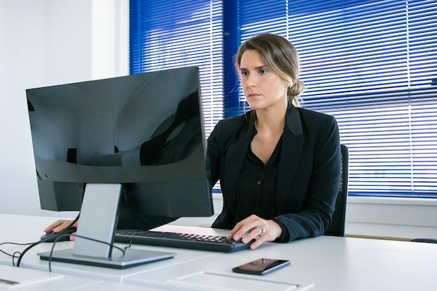 Fokussierte junge geschäftsdame, die in ihrem büro arbeitet, computer am arbeitsplatz benutzt und anzeige betrachtet. mittlerer schuss. konzept für digitale kommunikation oder unternehmensleiter