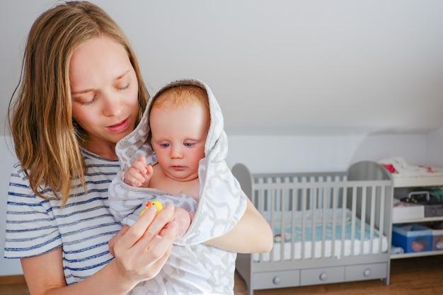 Fokussierte junge mutter, die süßes trockenes baby hält, das in kapuzenhandtuch nach dem duschen eingewickelt wird und mit gummibadespielzeug spielt. vorderansicht, kopierraum. kinderbetreuung oder badekonzept