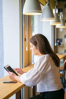 Fokussierte junge weibliche fachkraft, die tablette verwendet, während sie am schreibtisch im gemeinsamen arbeitsraum sitzt