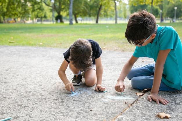 Fokussierte jungen sitzen und zeichnen mit bunten kreiden. konzept für kindheit und kreativität