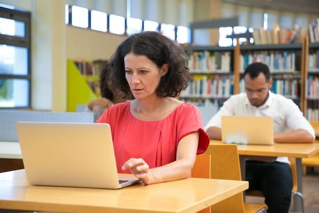 Fokussierte kaukasische frau, die laptop beim bei tisch sitzen betrachtet