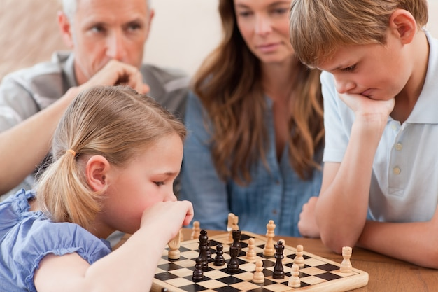 Fokussierte kinder, die schach vor ihren eltern spielen