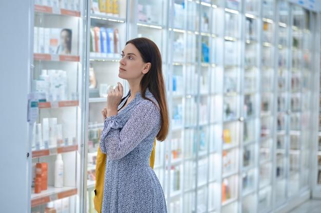 Fokussierte kundin, die sich in der drogerie für ein neues schönheitsprodukt entscheidet