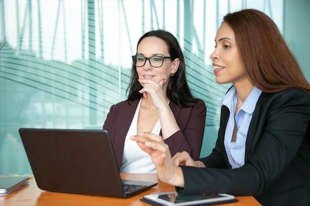 Fokussierte lächelnde geschäftsfrauen, die offenes laptop-display betrachten