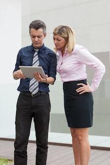 Fokussierte männliche und weibliche geschäftsleute, die draußen auf tablet-computer grasen.