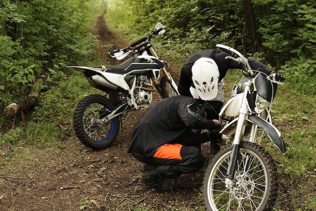 Fokussierte motorradfahrer in helmen, die gemeinsam den motorradmotor im wald überprüfen