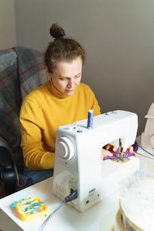 Fokussierte näherin mit nähmaschine an ihrem kreativen arbeitsplatz zu hause