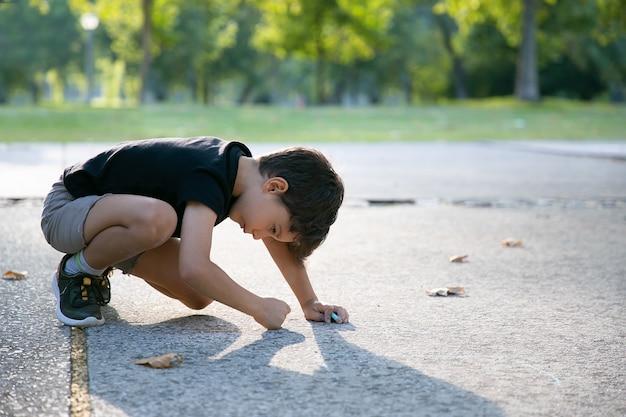 Fokussierte niedliche jungenzeichnung auf spielplatzoberfläche mit bunten kreidestücken. seitenansicht. konzept für kindheit und kreativität